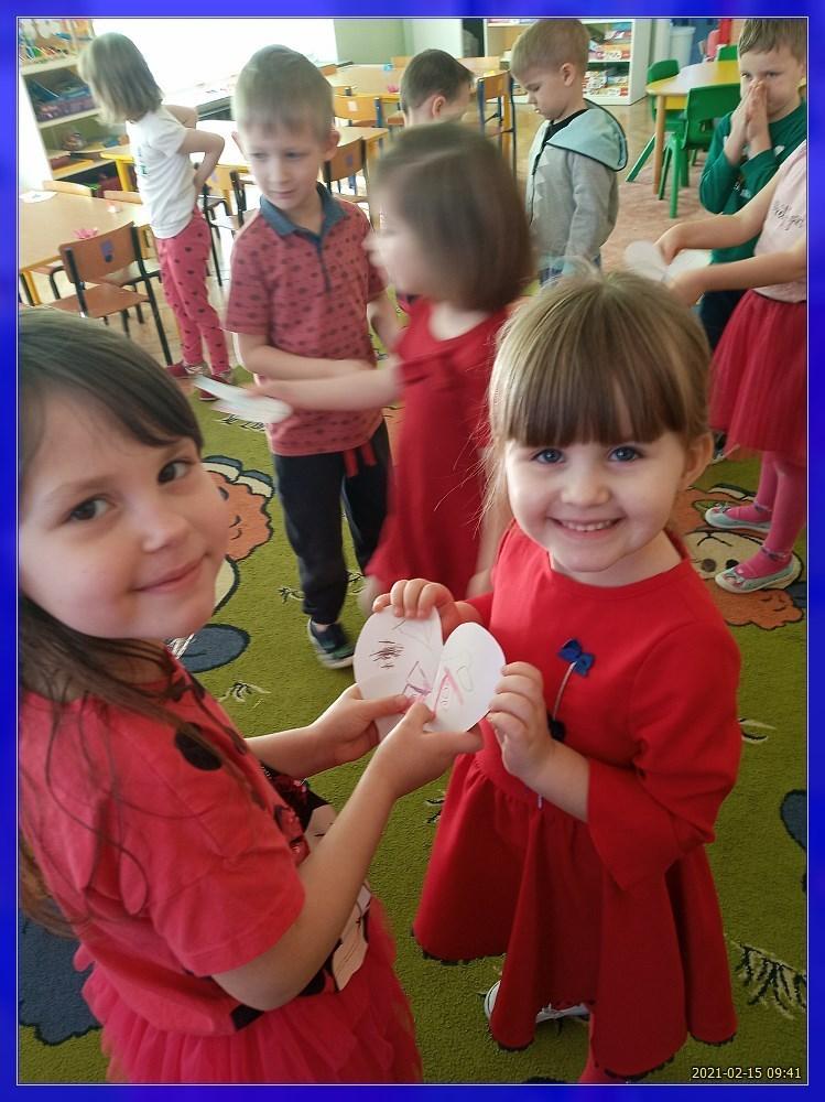 dwie dziewczynki łączą połówki papierowego serca