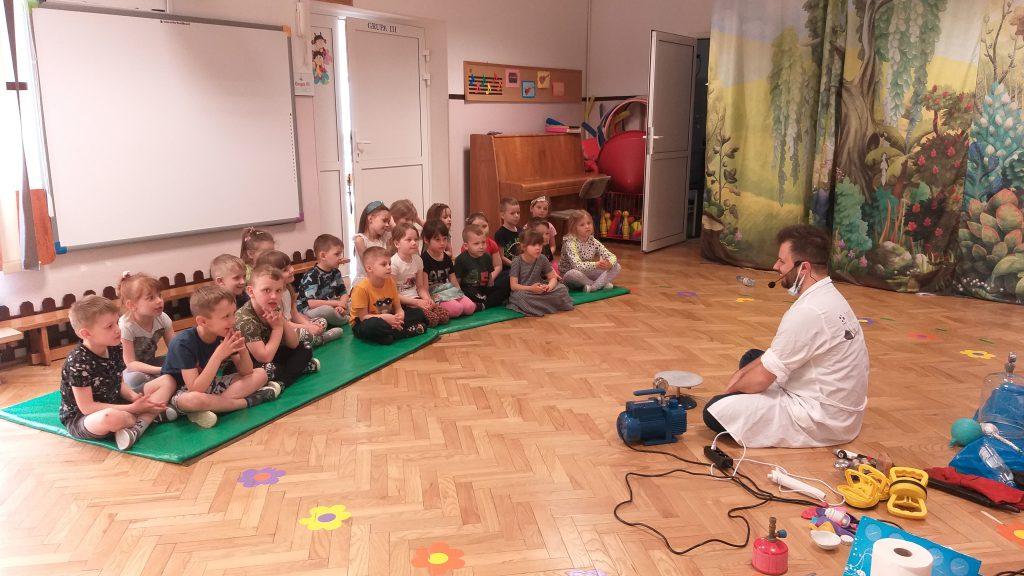 Dzieci siedzą i słuchają pana prowadzącego warsztaty.