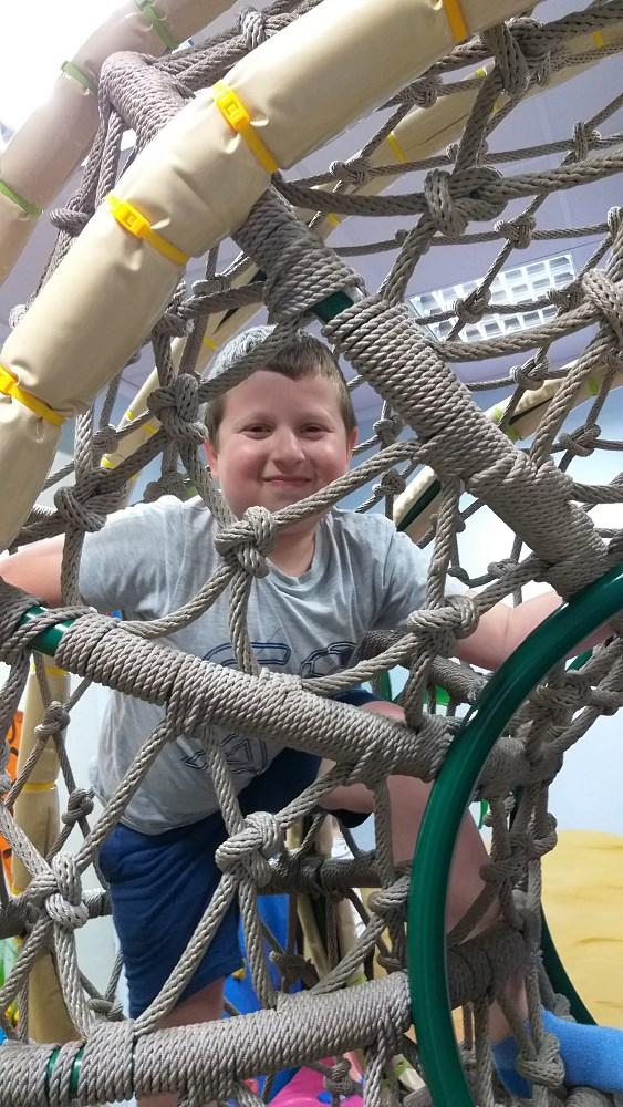 Chłopiec wspina się po sznurowej przeplotni.