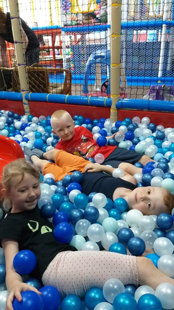 Troje dzieci podczas zabawy w basenie z kulkami.