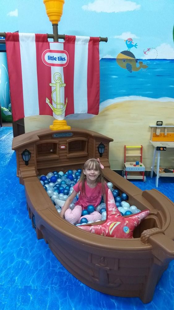 Dziewczynka pozuje w łodzi pirackiej z kulkami.