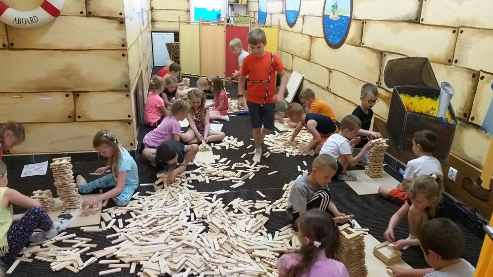 Duża grupa dzieci podczas konstruowania budowli z drewnianych klocków.