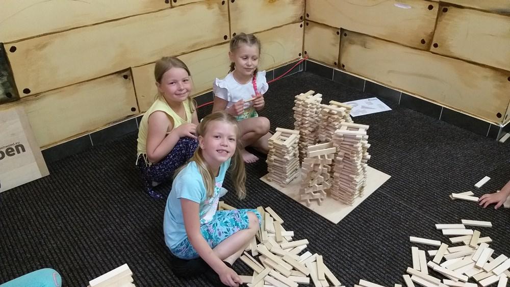 Trzy dziewczynki budują z drewnianych klocków.
