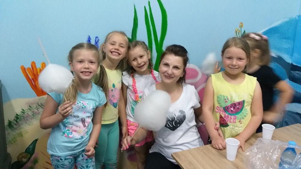 Cztery dziewczynki z nauczycielką podczas zajadania waty cukrowej.