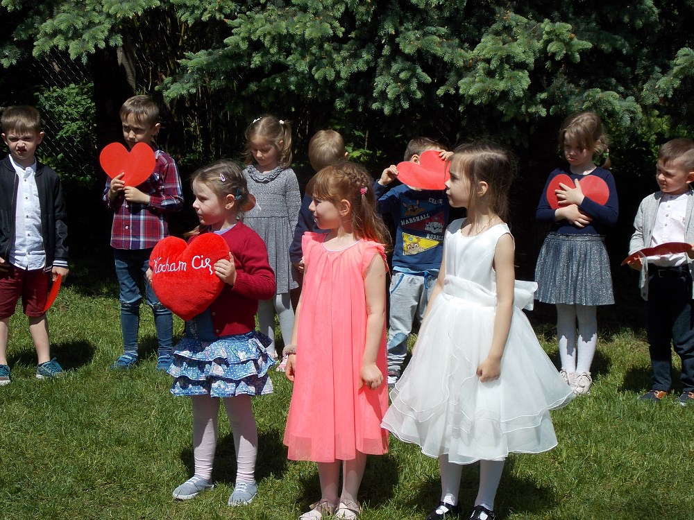 dzieci trzymają w rączkach czerwone serca i recytują wiersz