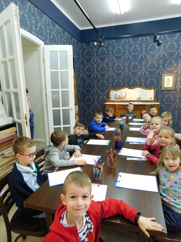 Dzieci siedzą przy stolikach.