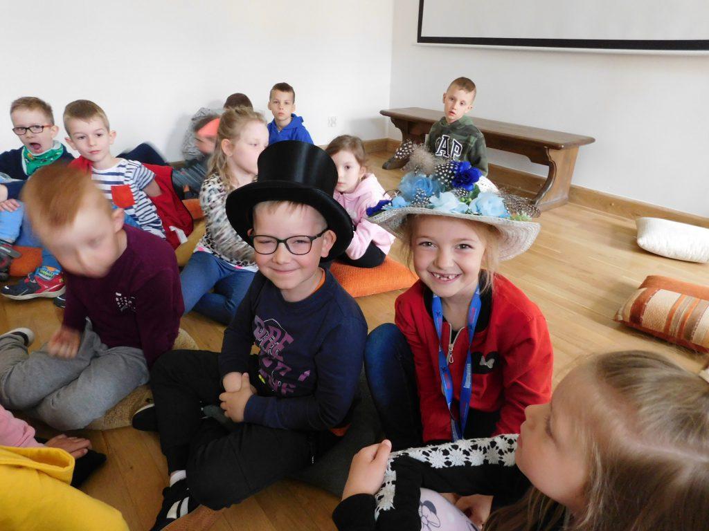 Dziewczynka i chłopiec siedzą w kapeluszach.