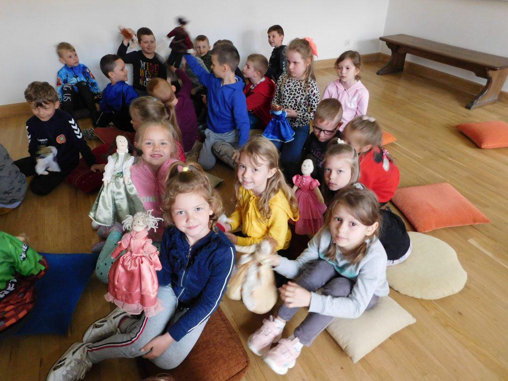 Dzieci siedzą, pokazując szmaciane lalki.