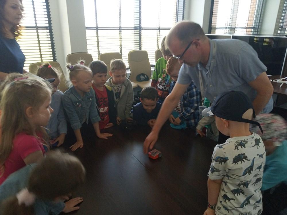 Nauczyciel demonstruje grupie dzieci działanie robota.