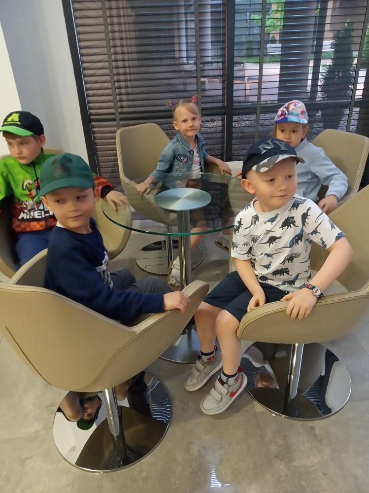 Pięcioro dzieci na fotelach przy szklanym stoliku.