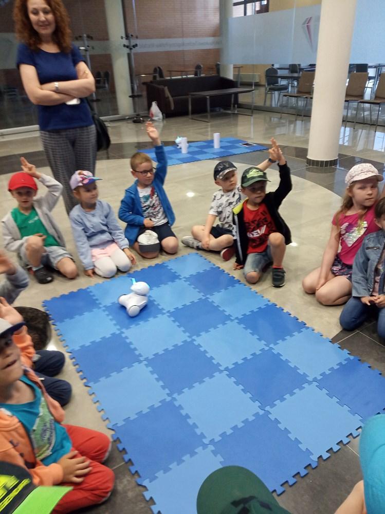 Grupa dzieci wokół maty, zgłaszają się do odpowiedzi.