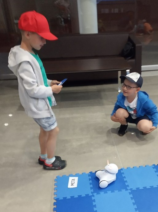 Dwóch chłopców podczas zabawy z robotem.