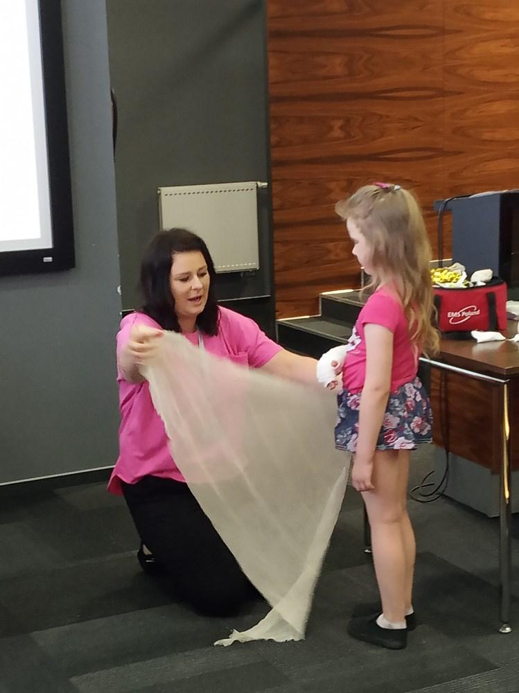 Nauczycielka demonstruje sposób zakładania chusty chirurgicznej na złamaną rękę.