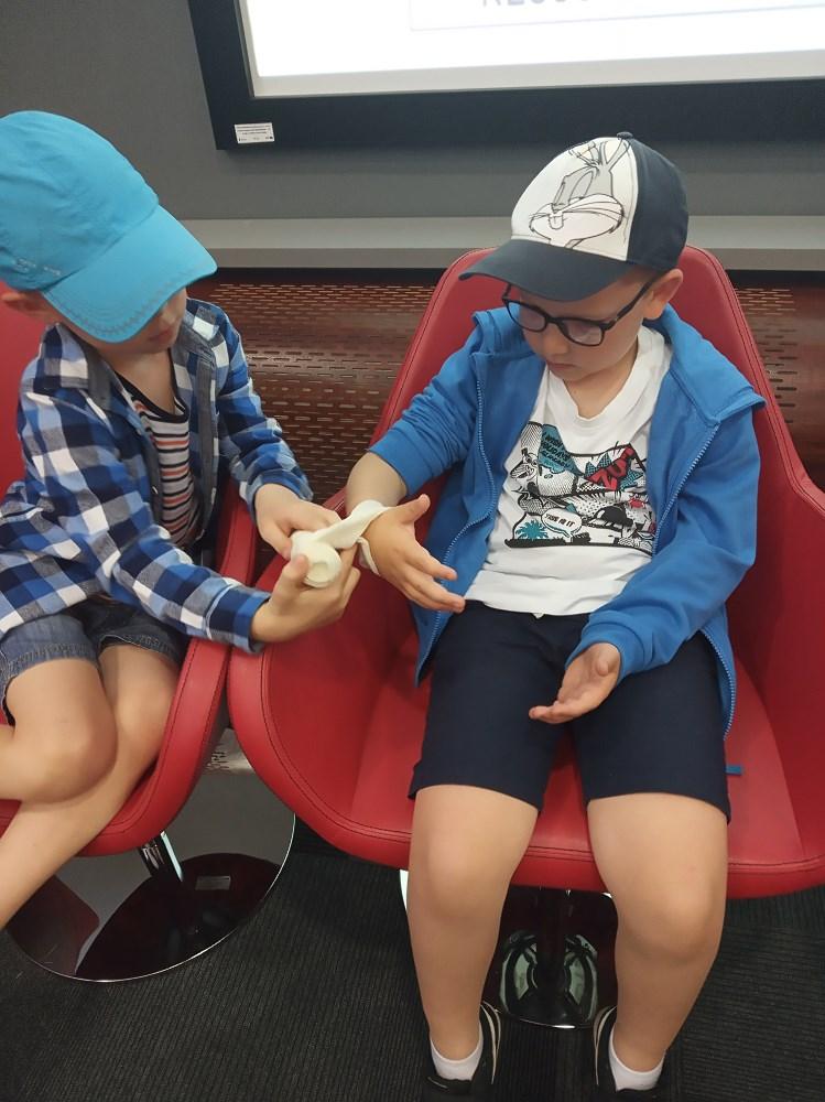 dwóch chłopców w trakcie ćwiczeń w zakładaniu opatrunku na rękę.